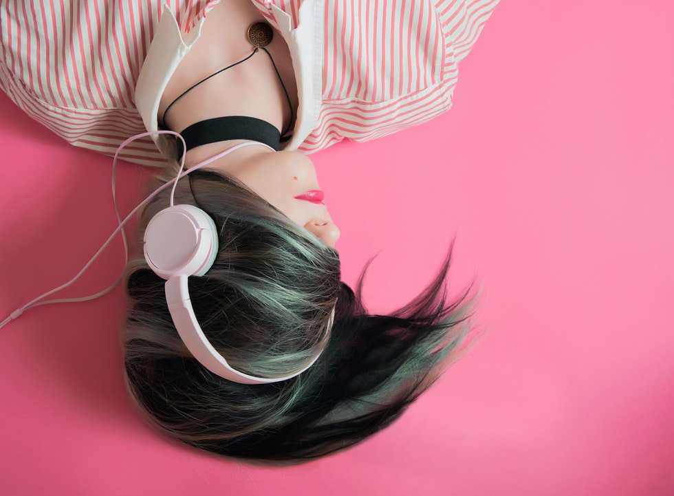 Stant Litore on audiobook - photo shows a listener with headphones against pink background - photograph by Elice Moore on Unsplash